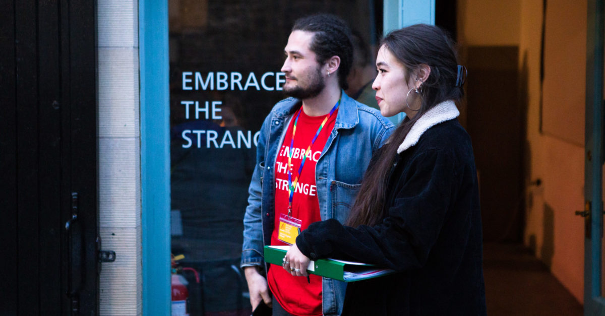 "Two people in their 20s stand at the entrance of a venue at Alchemy Film and Moving Image Festival ready to greet and welcome attendees. One wears an Alchemy t-shirt that reads ""Embrace the Strange"" and an LGBTQ pride lanyard. The other holds a clipboard. The words ""Embrace the Strange"" are also printed on the window of the festival venue."