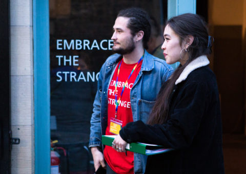 """Two people in their 20s stand at the entrance of a venue at Alchemy Film and Moving Image Festival ready to greet and welcome attendees. One wears an Alchemy t-shirt that reads """"Embrace the Strange"""" and an LGBTQ pride lanyard. The other holds a clipboard. The words """"Embrace the Strange"""" are also printed on the window of the festival venue."""