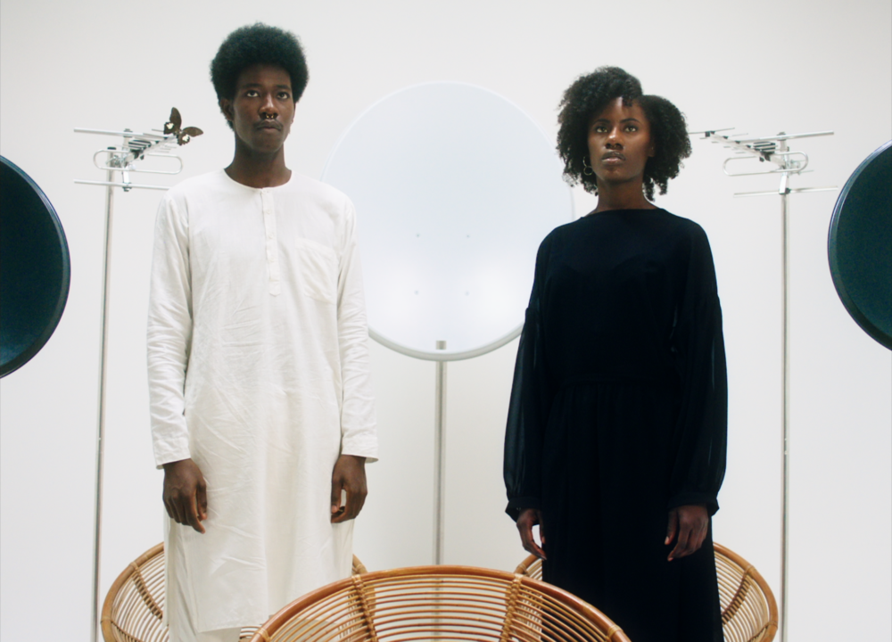 A Black man and woman stand behind a wicker chair and in front of a satellite dish, wearing plain clothes - the man in all white and the woman in all black.