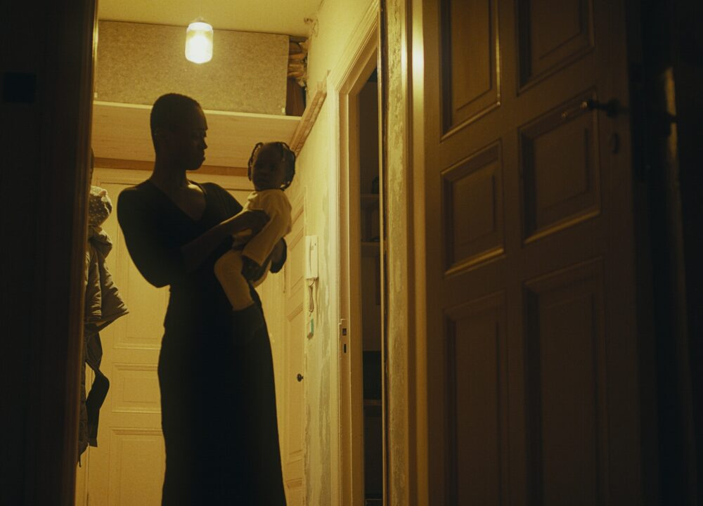 A black woman with short hair stands in a hallway holding a child.