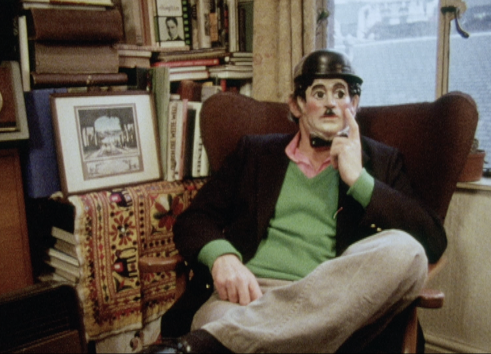A man sits in a chair holding a plastic mask of Charlie Chaplin to his face. The mask includes a black bowler hat and Charlie Chaplin's famous mustache, shorter than the mask's mouth.
