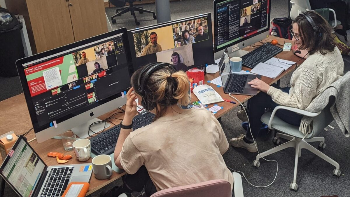 Two people sit in office chairs,, each an iMac and both with laptops, to deliver a livestream during Alchemy Film and Moving Image Festival 2021.